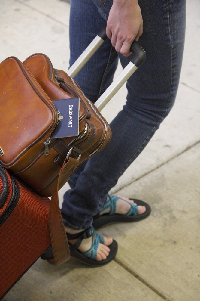 A red suitcase and a leather boarding bag - Best underseat carry on