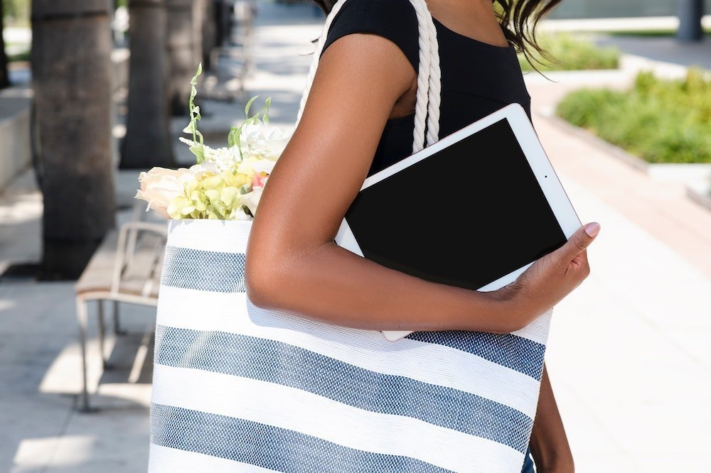 A woman with a tote bag and an iPad