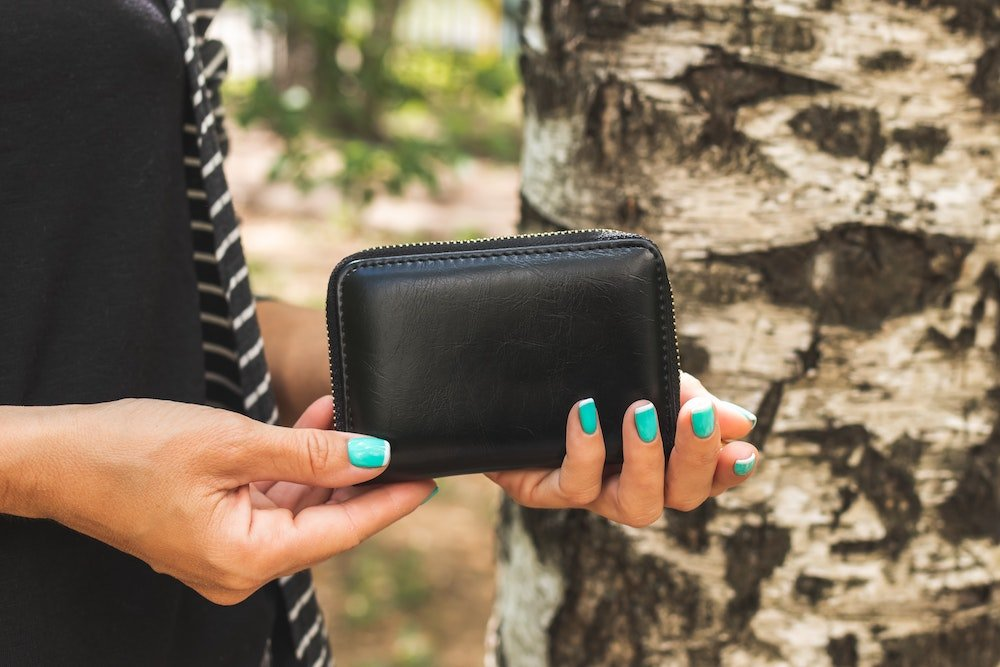 Woman holding a black wallet