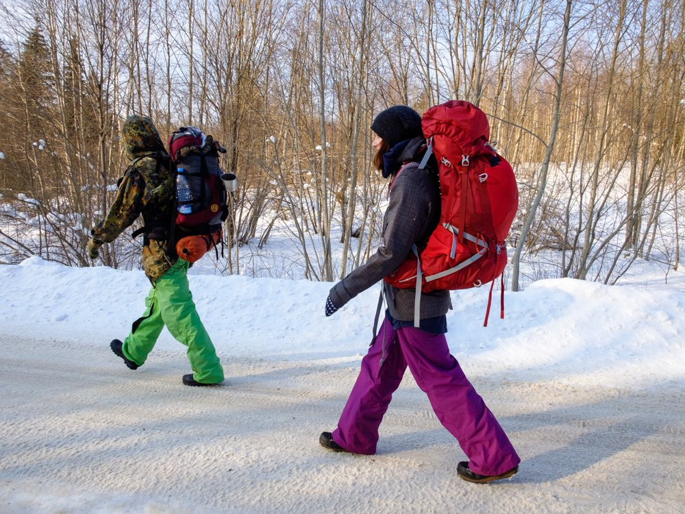 People with backpacks walking on the road