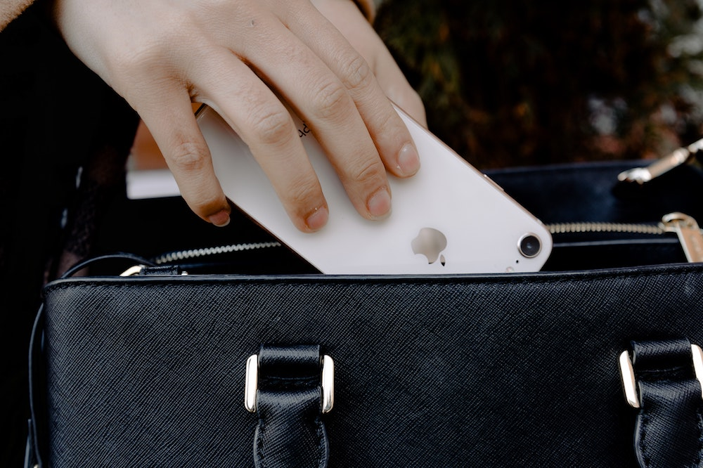 A woman putting a phone in a bag