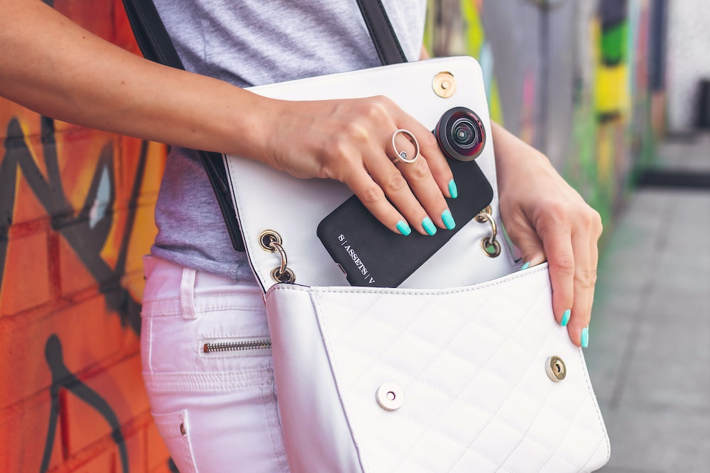 A woman putting a phone in her handbag