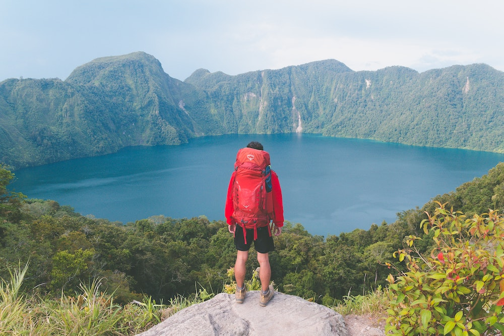 A man with a red Osprey hiking backpack