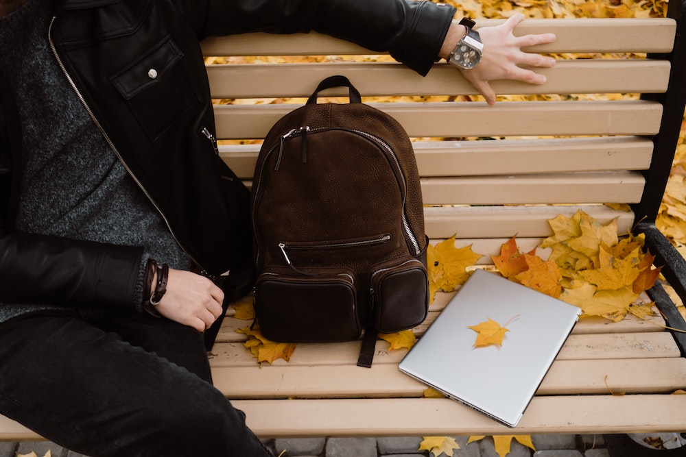 A laptop and backpack on the bench
